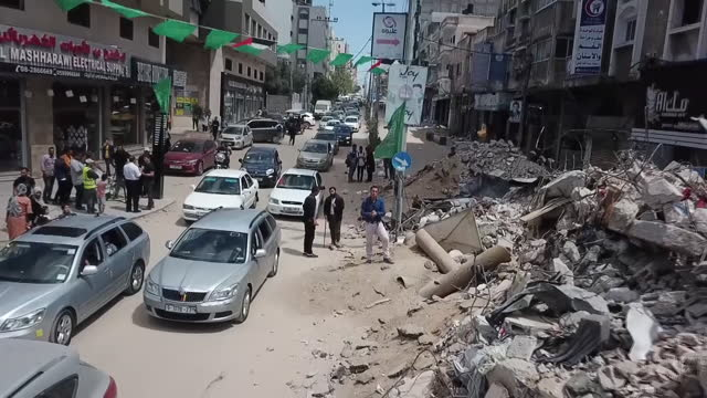 shows drone shots aftermath of israeli airstrikes, rubble and debris everywhere, exterior shots gaza residents clearing up the mess and returning to... - ガザ市点の映像素材/bロール