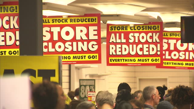 vídeos de stock, filmes e b-roll de shows exterior and interior shots customers walking in and out of closing bhs store posters and signs advertising price reductions shop fixtures for... - último dia
