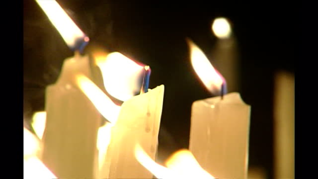 shows exterior close up shots flames on candles fluttering in the breeze at night timeat candlelit vigil to victims of the bali bombing in kuta on... - monumento commemorativo temporaneo video stock e b–roll