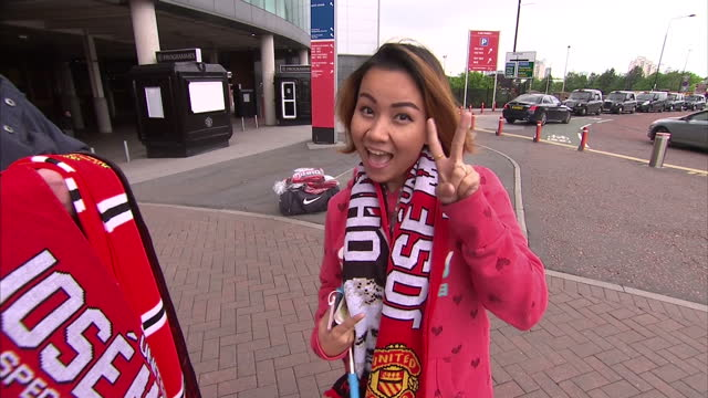 shows exterior close up shots jose mourinho's face on man u scarf and tourist buying scarf and posing for camera with fingers in v sign on may 27... - neckwear stock videos and b-roll footage