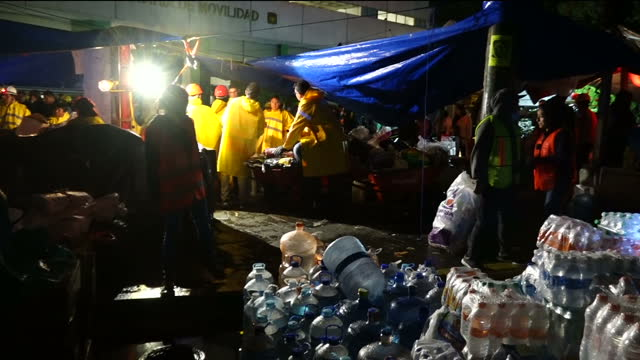 Shows exterior night shots a large pile of bottled water gathered near rescue operation with floodlightts erected in background so rescue effort can...