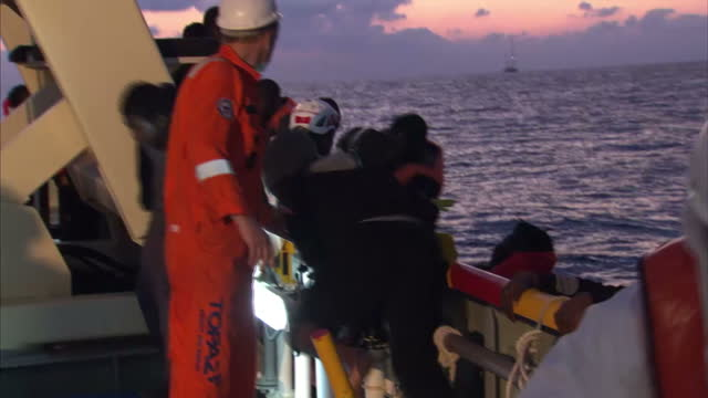 stockvideo's en b-roll-footage met shows exterior night shots african migrants sitting on flimsy boat off libyan coast with moas rescuers shouting instructions at them. exterior shots... - red sea