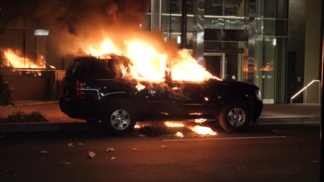 shows exterior night shots burning car as protesters gathered on the streets of washington dc facing off with riot police over the death of george... - riot stock videos & royalty-free footage