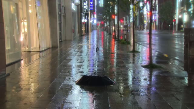 shows exterior night shots heavy rain falling in deserted streets as typhoon hagibis arrives, with lights reflected in water. one person is dead, at... - typhoon stock videos & royalty-free footage