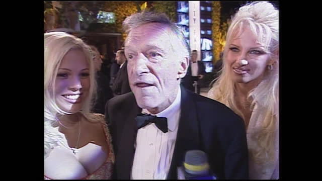 shows exterior night shots interview with hugh hefner with some of the playboy bunnies, and them posing for photos at the vanity fair oscars party,... - vanity fair stock videos & royalty-free footage