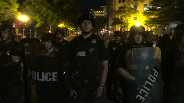 shows exterior night shots lines of police officers wearnig riot gear standing across road at night in washington dc as people protest over the death... - 機動隊点の映像素材/bロール