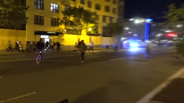 shows exterior night shots looters running out of pharmacy and protesters running down road as motorbike police arrive at scene, people protesting in... - looting stock videos & royalty-free footage