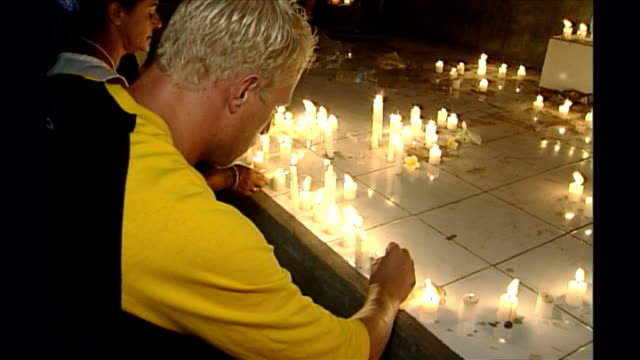 shows exterior night shots man lighting candle and looking very upset at candlelit vigil to victims of the bali bombings in kuta on october 14th 2002... - monumento commemorativo temporaneo video stock e b–roll