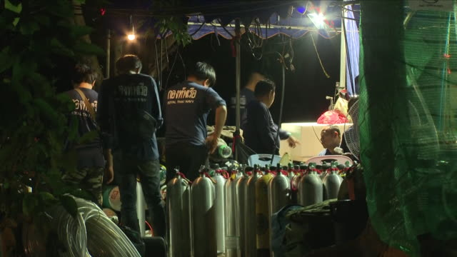 Shows exterior night shots members of the diving team preparing oxygen tanks at base of operations The death of an experienced diver inside the cave...