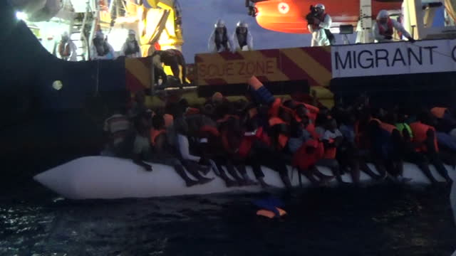 Shows exterior night shots migrants sitting in an overcrowded rubber dinghy with only a few wearing life jackets as it is tied alongside Migrant...