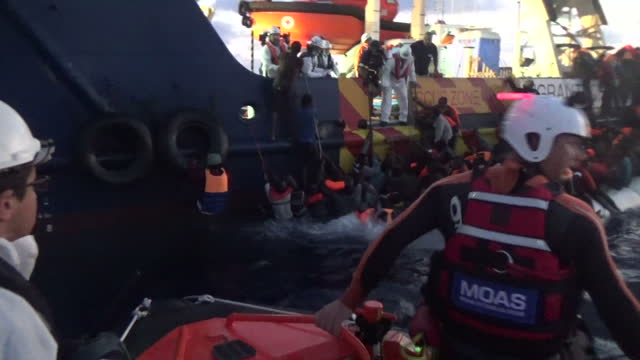shows exterior night shots moas rescue worker jumping off small boat into water and swimming towards migrants in water after the dinghy they were in... - mittelmeer stock-videos und b-roll-filmmaterial