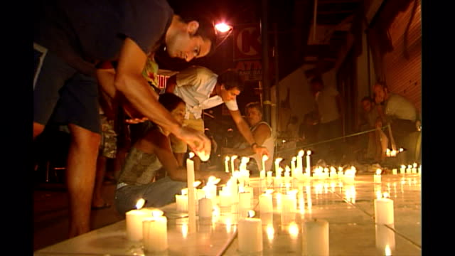 shows exterior night shots mourners lighting candles and people looking sad at candlelit vigil to victims of the bali bombings in kuta on october... - monumento commemorativo temporaneo video stock e b–roll