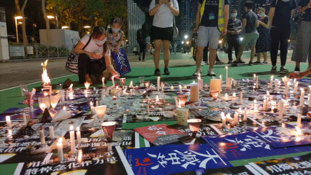 shows exterior night shots people lighting candles at a quiet, socially-distanced, non-violent vigil in vicotria park, hong kong, to commemorate the... - tiananmen square stock videos & royalty-free footage