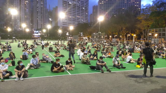 shows exterior night shots people sitting in quiet, socially-distanced, non-violent vigil in vicotria park, hong kong, to commemorate the 31st... - tiananmen square stock videos & royalty-free footage
