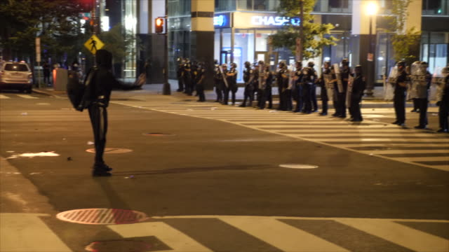 shows exterior night shots protester moving forward to confront line of riot police at night protests over the death of george floyd. clean-up... - protestor stock videos & royalty-free footage