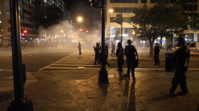 shows exterior night shots protesters gathered on the streets of washington dc, facing off with riot police standing in line across the road, smoke... - tear gas stock videos & royalty-free footage