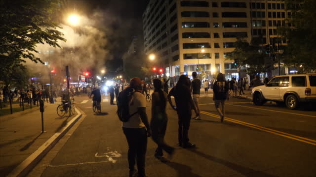 shows exterior night shots protesters gathered on the streets of washington dc, facing off with riot police and standing shouting over the death of... - protestor stock videos & royalty-free footage