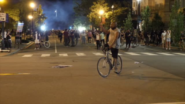 shows exterior night shots protesters gathered on the streets of washington dc, facing off with riot police and standing shouting over the death of... - tear gas stock videos & royalty-free footage