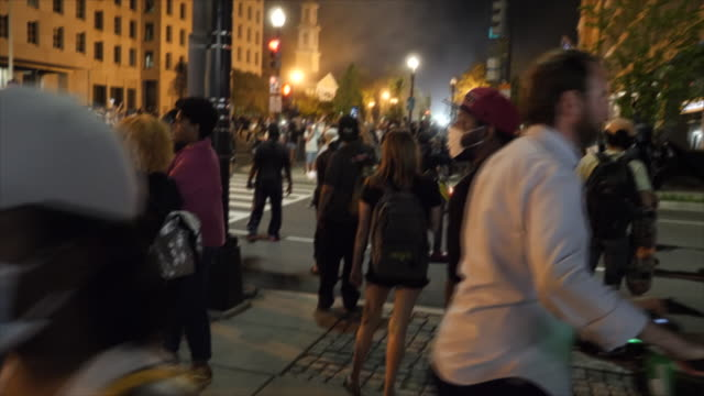 shows exterior night shots protesters gathered on the streets of washington dc, facing off with riot police, and standing shouting over the death of... - tear gas stock videos & royalty-free footage