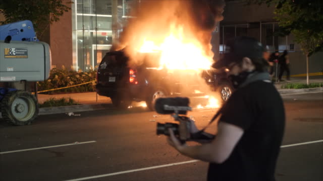 shows exterior night shots riot police moving protesters along street and burning car in washington dc, over the death of george floyd. clean-up... - protestor stock videos & royalty-free footage