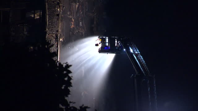 shows exterior night shots water from fire crew hose illuminated by floodlight as it is aimed at exterior of grenfell tower block after the fire has... - fire hose stock-videos und b-roll-filmmaterial