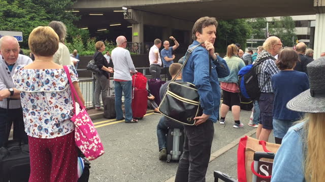 shows exterior point of view shots walking through crowd of passengers with luggage outside manchester airport following bomb scare on 5th july 2017... - flugpassagier stock-videos und b-roll-filmmaterial