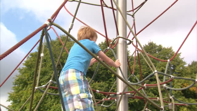 shows exterior shot of young boy climbing up climbing frame on august 31, 2014 in unspecified, united kingdom. - プロトン点の映像素材/bロール