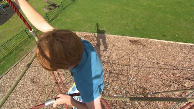 shows exterior shot of young boy climbing up towards the top of a climbing frame on august 31, 2014 in unspecified, united kingdom. - プロトン点の映像素材/bロール