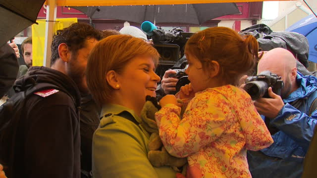 Shows exterior shote SNP Leader Nicola Sturgeon holding toddler in her arms and talking to group of young children including girl who shows a picture...