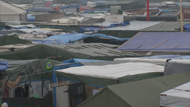 shows exterior shots across rooftops of tents and shelters in the calais jungle migrant camp and few migrants walking around inside the official... - calais stock videos and b-roll footage