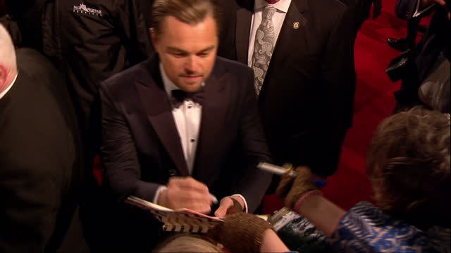 shows exterior shots actor leornardo dicaprio signing autographs and walking on red carpet the 2016 baftas film awards ceremony at was held at... - leonardo dicaprio stock videos & royalty-free footage