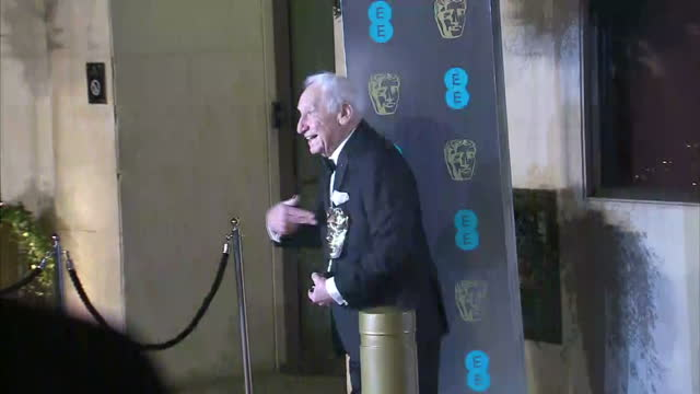 Shows exterior shots actor Mel Brooks holding his Academy Fellowship Award statue at the BAFTA Awards posing for photos and talking to press on 12th...