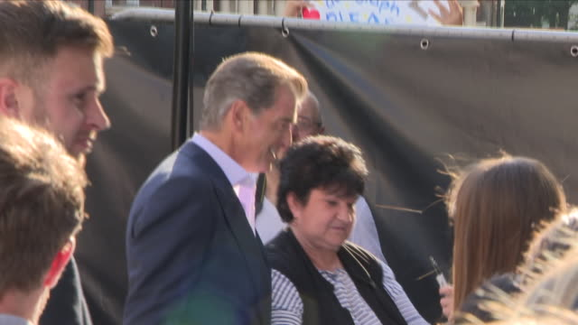 Shows exterior shots actor Pierce Brosnan signing autographs at the 'blue' carpet British Premiere of the film sequel Mamma Mia Here We Go Again on...