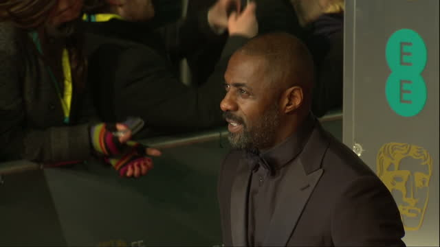 Shows Exterior shots actors Idris Elba and Warren Brown talking and Idris Elba posing for photos on red carpet The 2016 BAFTAS Film Awards ceremony...