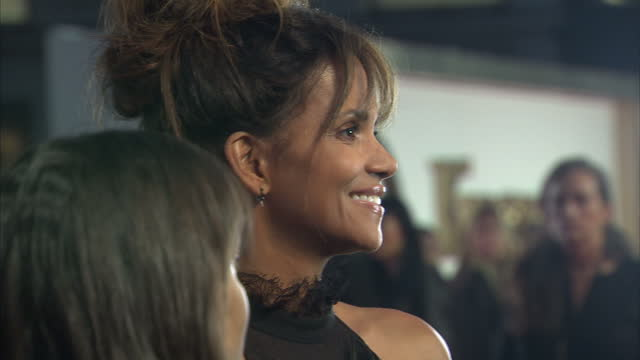 vídeos de stock, filmes e b-roll de clean shows exterior shots actress halle berry signing autographs and talking to fans on the orange carpet at the world premiere of 'kingsman the... - halle berry