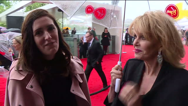 Shows exterior shots actress Joanna Lumley walking with umbrella on red carpet and interview with her speaking on British weather and receiving BAFTA...