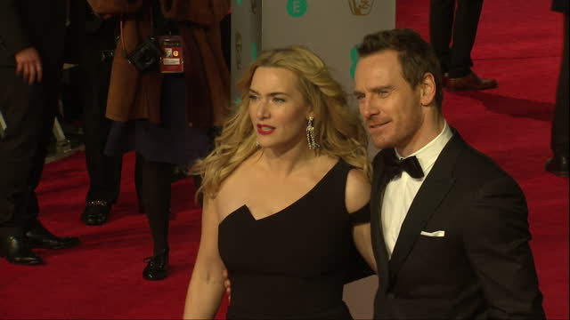 shows exterior shots actress kate winslet posing for photos on red carpet and joined by actor michael fassbender. the 2016 baftas film awards... - kate winslet stock videos & royalty-free footage