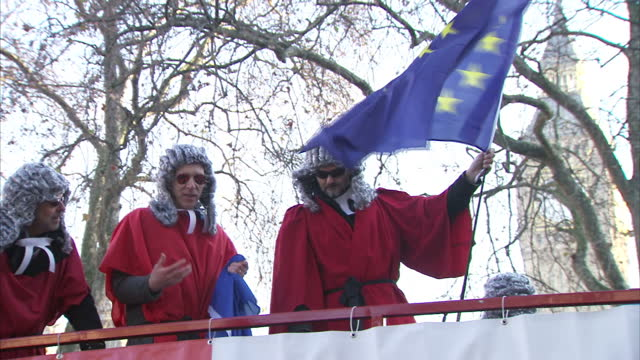 shows exterior shots anti-brexit protesters from the 'britain for europe' campaign dressed as judges holding eu flags standing on top of red open top... - stationary stock videos & royalty-free footage