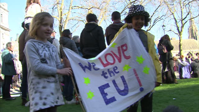 Shows exterior shots antiBrexit protesters gathered in Parliament Square in front of the Houses of Parliament in London holding signs and EU flags to...