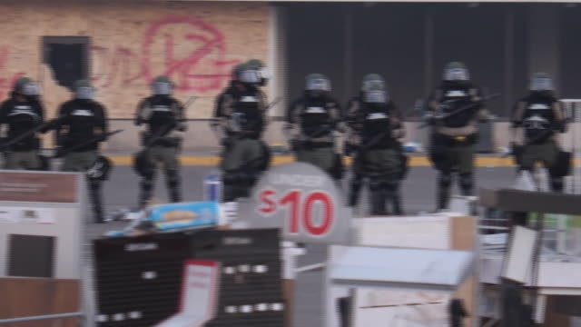 shows exterior shots armed riot police officers advancing through debris left by protesters gathered outside police station in minneapolis it's been... - 機動隊点の映像素材/bロール