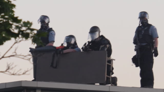 shows exterior shots armed riot police officers on roof of building as protesters gather outside police station in minneapolis. it's been another... - tear gas stock videos & royalty-free footage