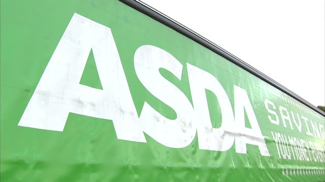 stockvideo's en b-roll-footage met shows exterior shots asda arctic lorry farmer walking a cow with 'what is my future' painted on it's side on august 09 2015 in wigan united kingdom - dairy product