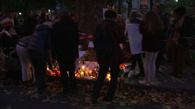 shows exterior shots at dusk police officers watching and directing as people move candles and flowers to outside the bataclan cafe exterior shots... - terrorism bildbanksvideor och videomaterial från bakom kulisserna