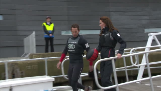 shows exterior shots bar's test boat t1 a foiling ac45 catamaran being lowered into water next to dock and catherine duchess of cambridge walking... - fluggastbrücke stock-videos und b-roll-filmmaterial