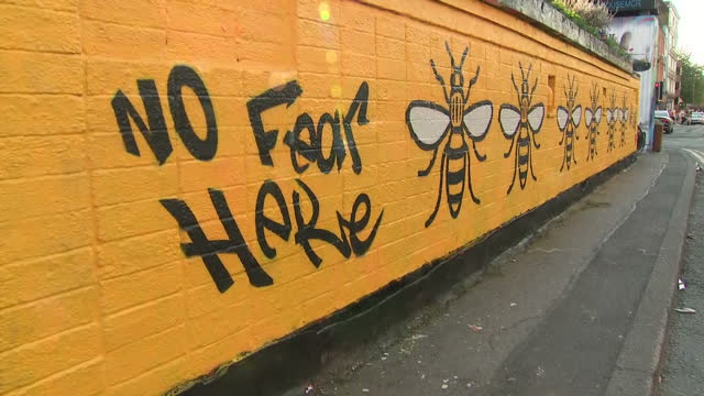 Shows exterior shots Bee mural w/ words 'No Fear Here' and phrase'#We Are Manchester #We Stand Together' with pan up to sun shining in sky People...