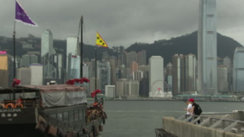 shows exterior shots boats including a star ferry sailing across victoria harbour as storm clouds arrive overhead and light starts to fade, on 3rd... - star ferry stock-videos und b-roll-filmmaterial
