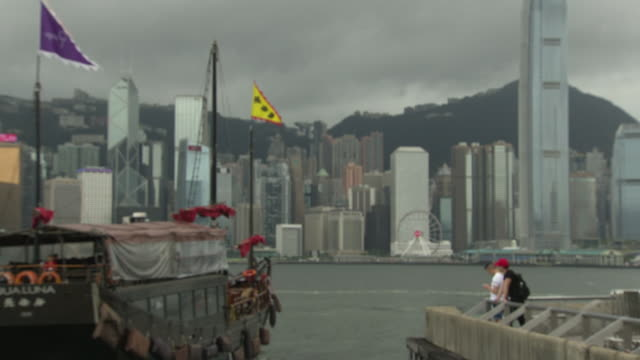 stockvideo's en b-roll-footage met shows exterior shots boats including a star ferry sailing across victoria harbour as storm clouds arrive overhead and light starts to fade on 3rd... - star ferry