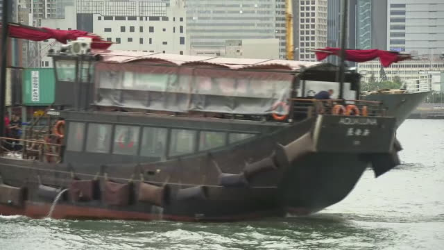 shows exterior shots boats sailing across victoria harbour, on 3rd july, 2019 in hong kong, china - dschunke stock-videos und b-roll-filmmaterial