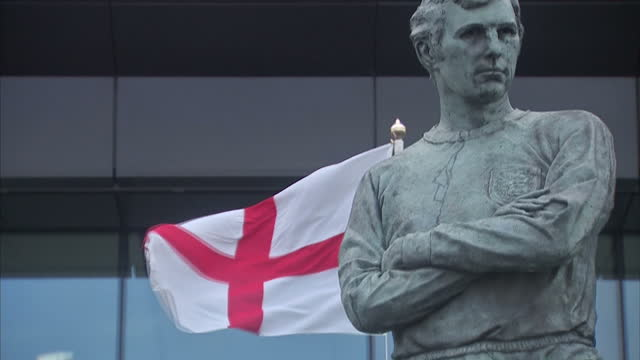 shows exterior shots bobby moore statue outside wembley stadium, english flag and stadium lighting on november 13, 2015 in london, england. - statue stock videos & royalty-free footage
