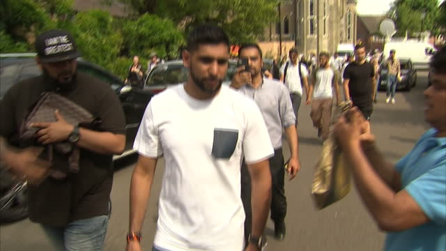 shows exterior shots boxer amir khan speaking about grenfell tower fire as person films him on mobile phone. locals and volunteers have claimed that... - co ordination stock videos & royalty-free footage